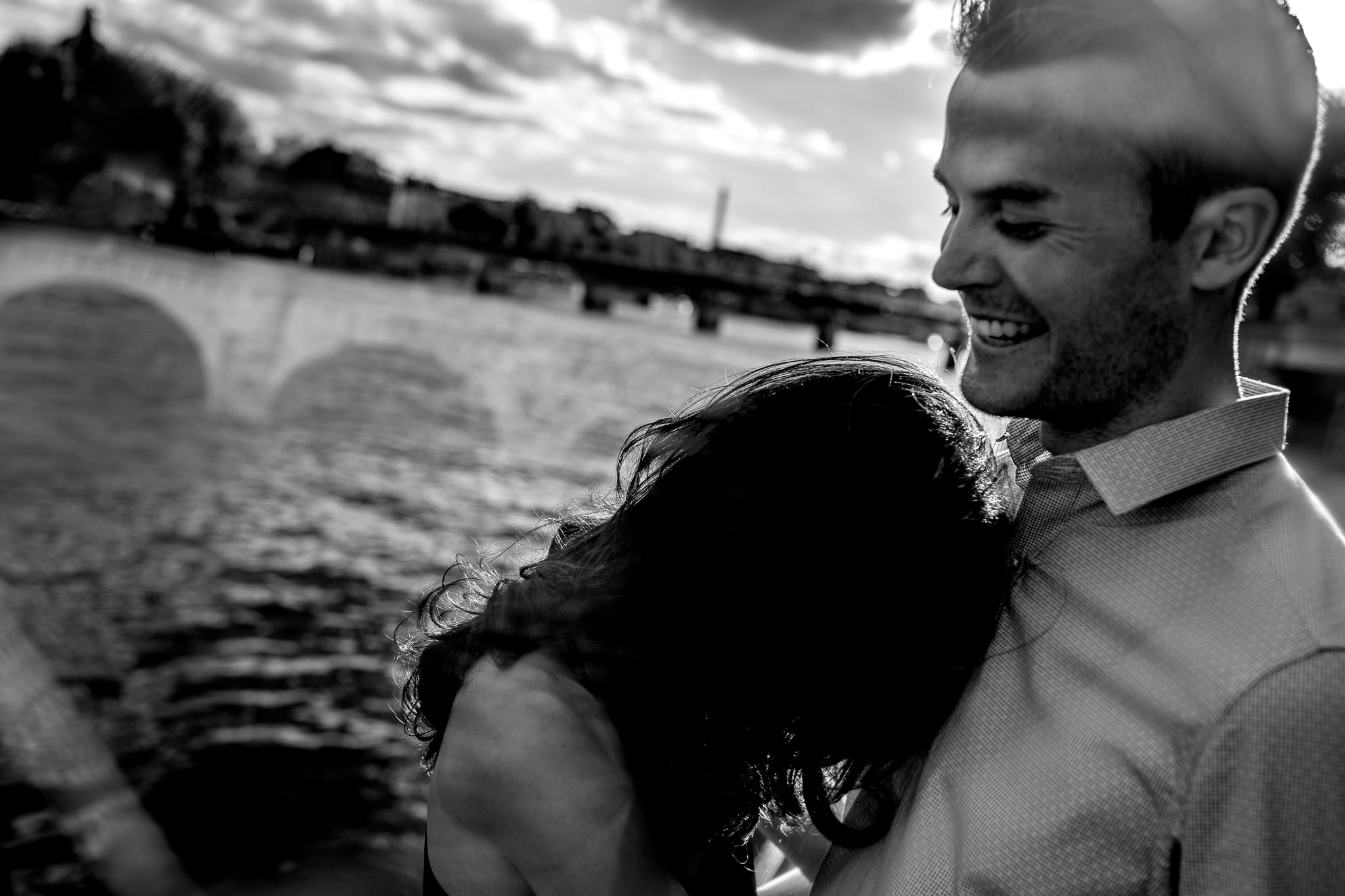 Engagement photo on oldest bridge in Paris France with groom to be laughing