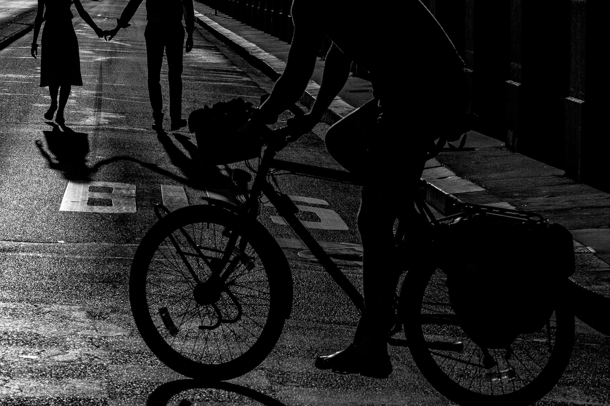 Engagement photo in Paris of couple walking with silhouette and bike rider
