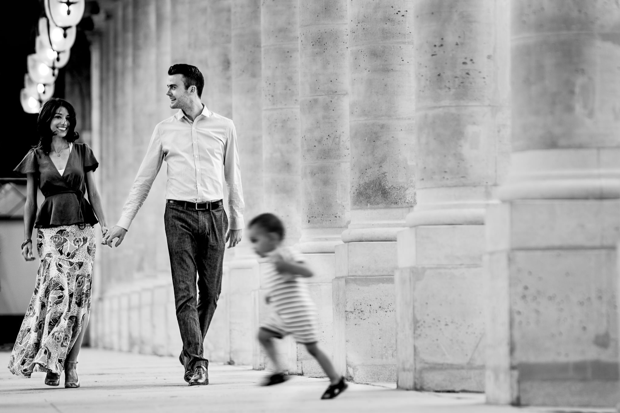 Engagement photo in Paris with child running in foreground
