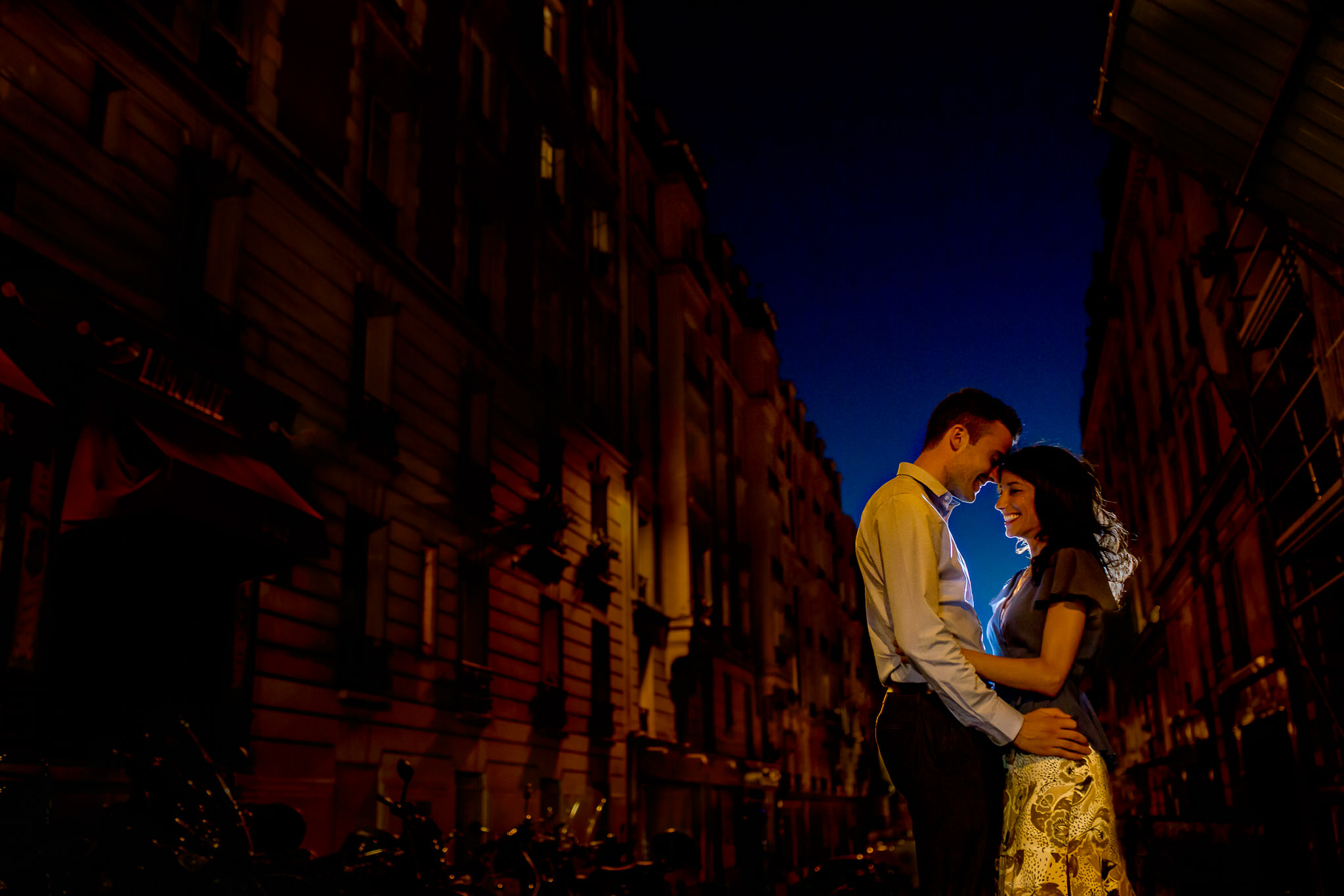 Engagement photo in Paris low light in streets with blue sky