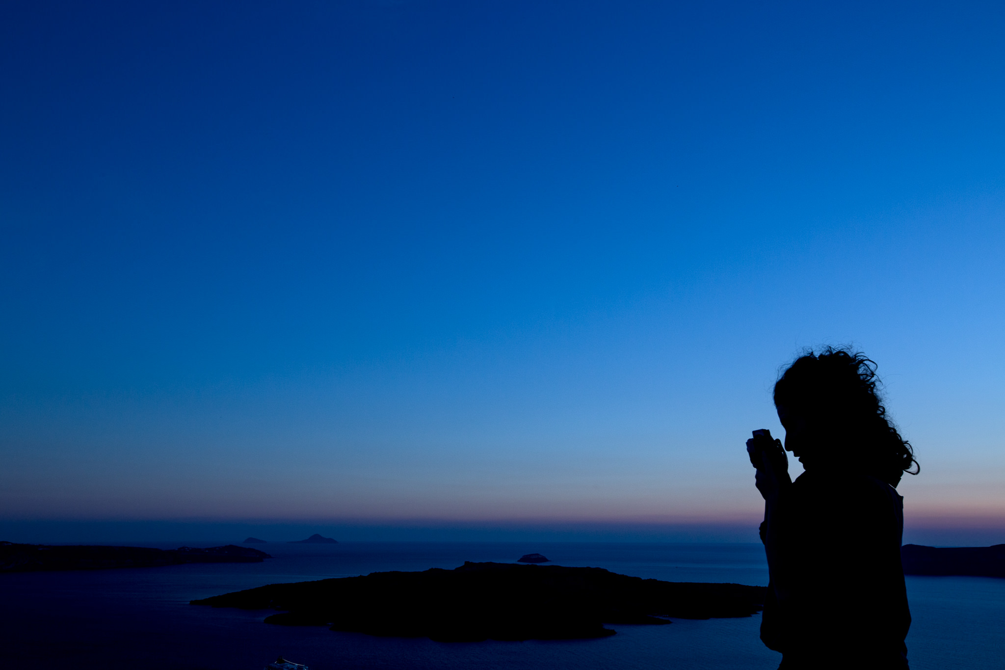 Photographer at sunset on Santorini in Thira