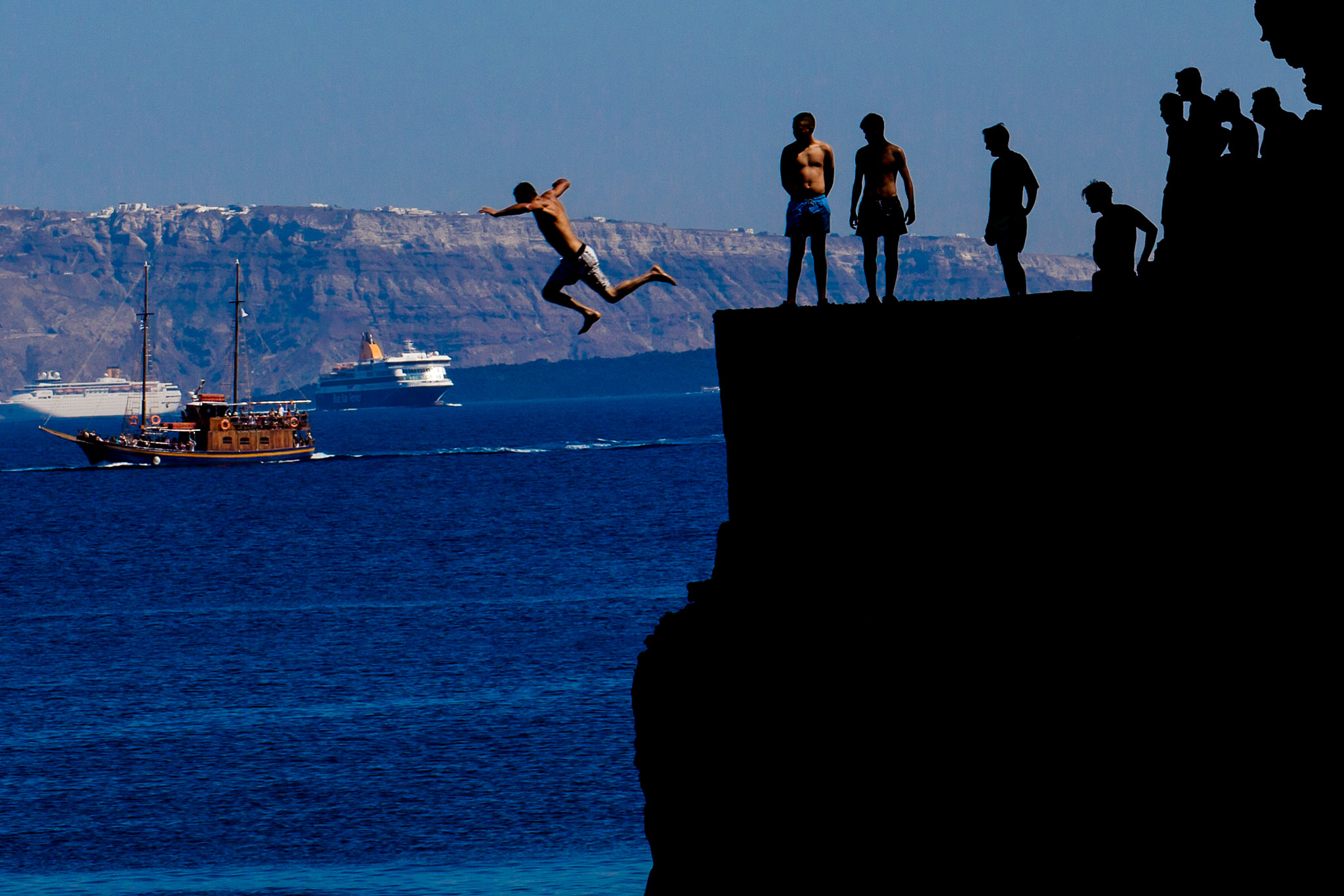 Silhouette photograph of men jumping off cliff on Santorini Greece into ocean