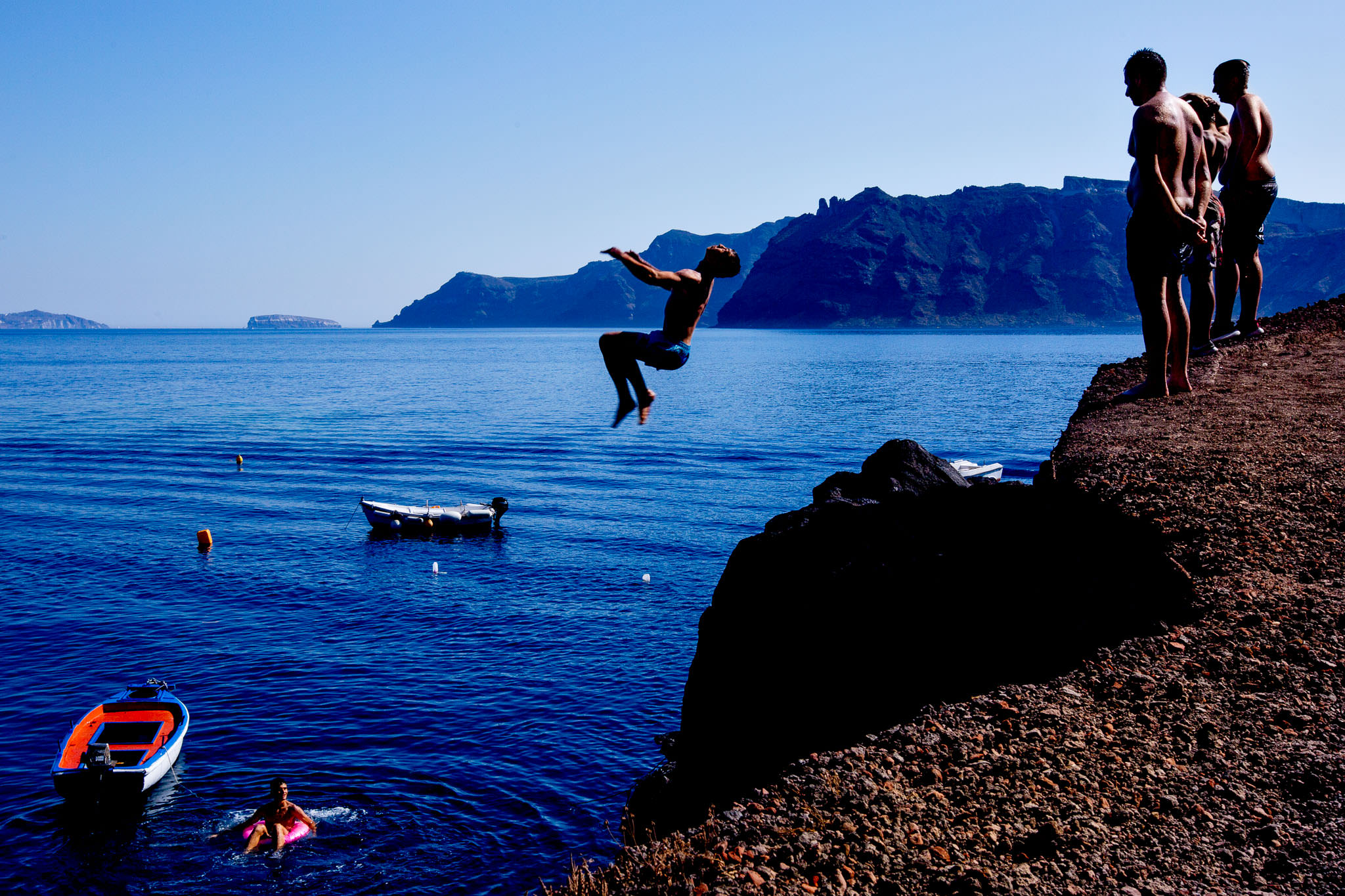 Man flipping off cliff into ocean on Santorini Greece