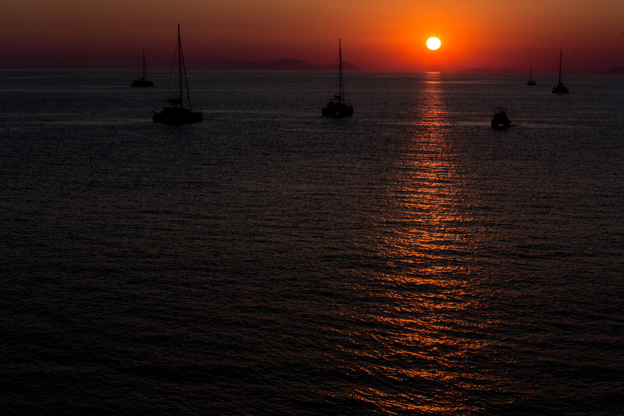 Sunset with silhouette sailboats on ocean near Oia