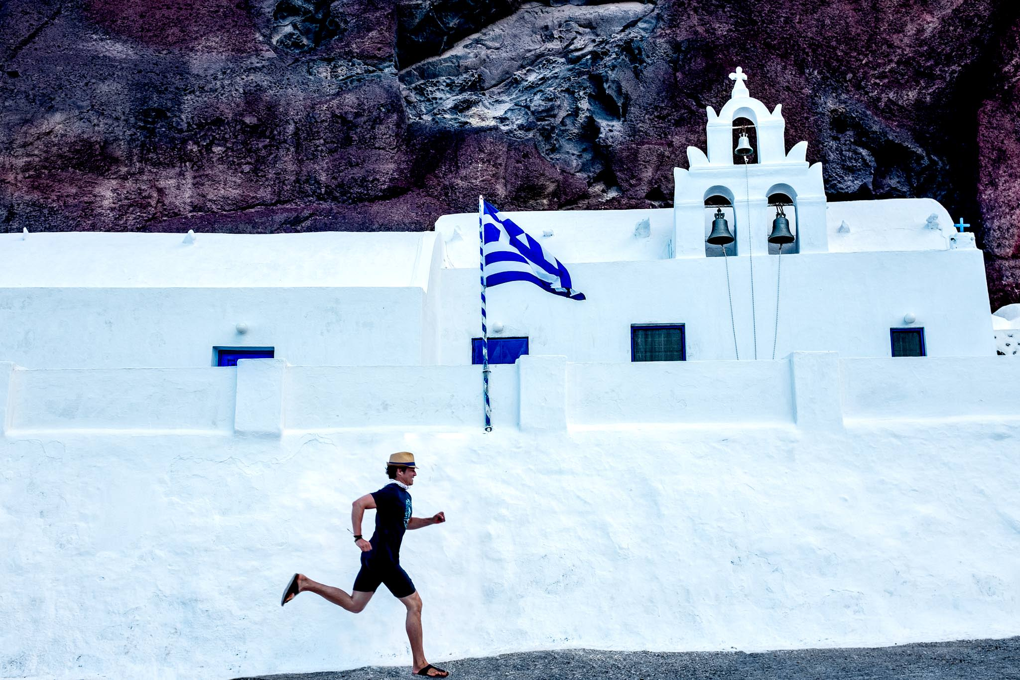 Man running near Greek church on Santorini Greece
