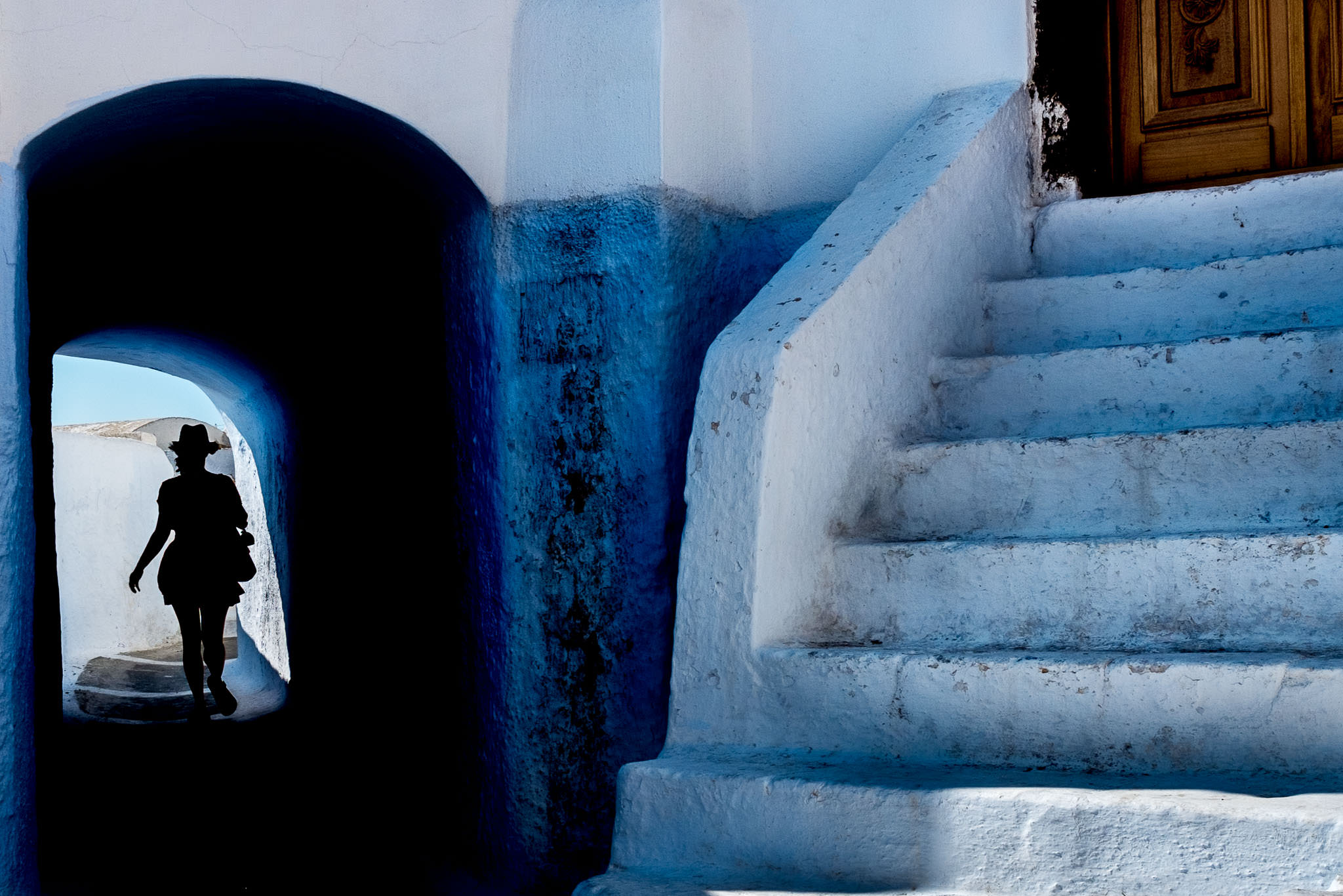 Woman silhouetted walking through tunnel in backstreet Santorini Greece