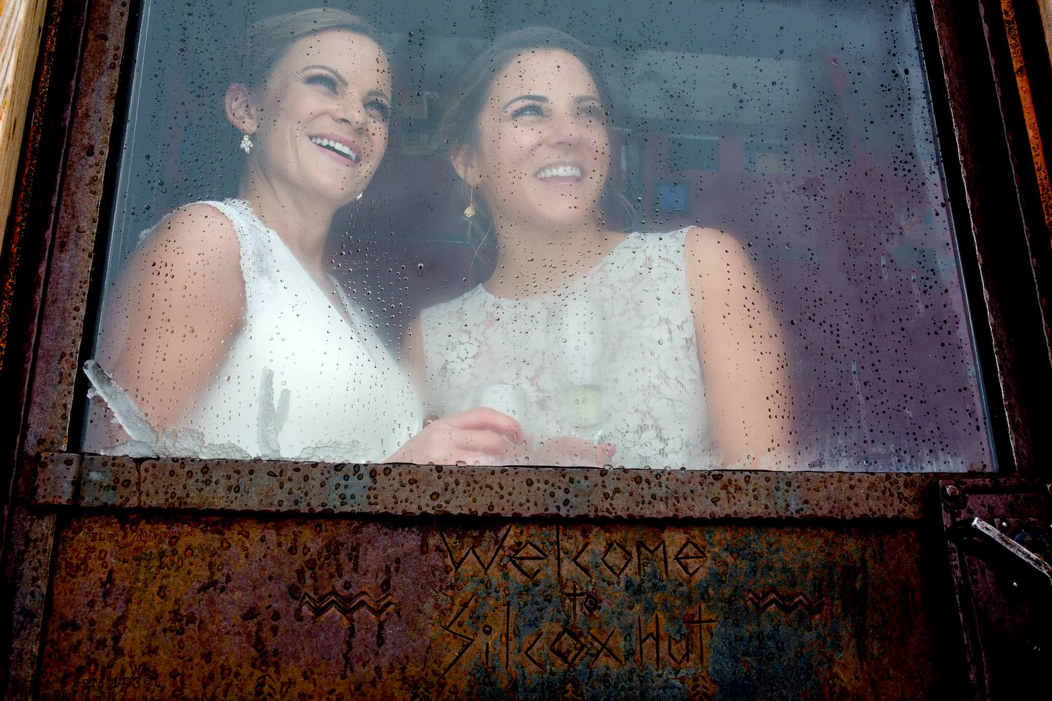 Bride and bridesmaid looking out window at Silcox Hut at Timberline Lodge