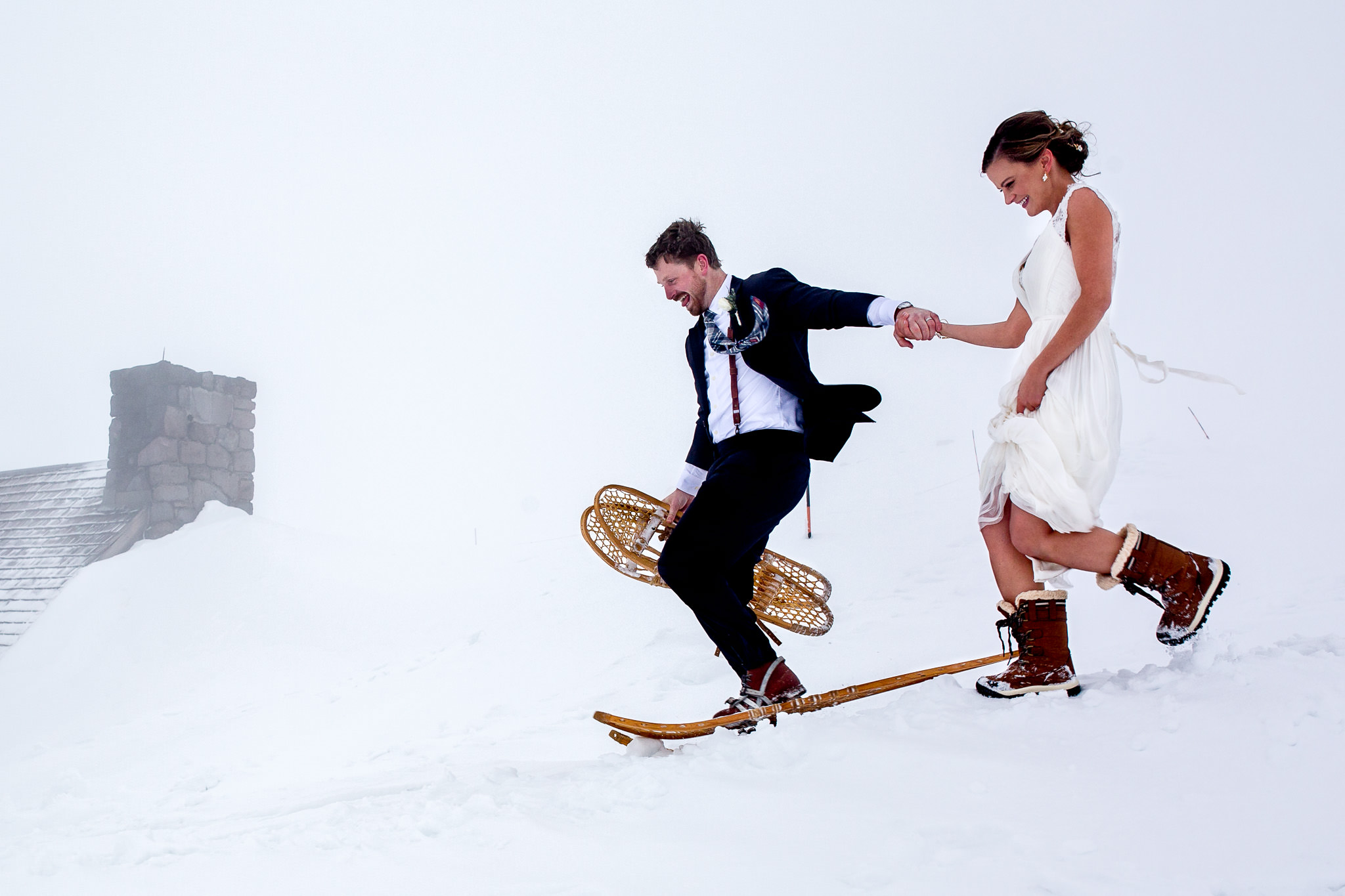 Bride and Groom snowshoeing and laughing atop Mt Hood at Timberline Lodge