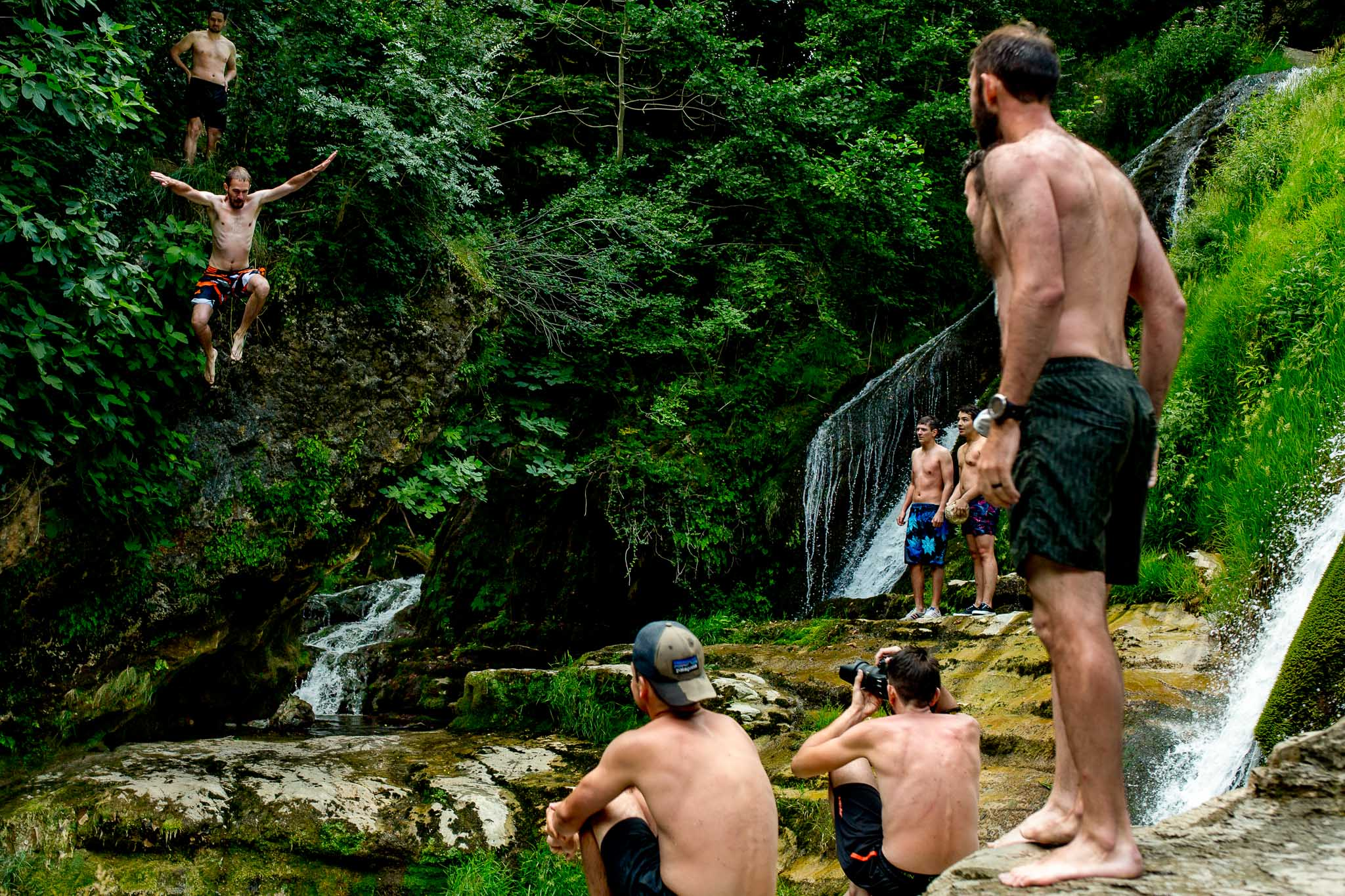 Groomsmen jumping into river in Cirque de Navacelles outside Montpellier France