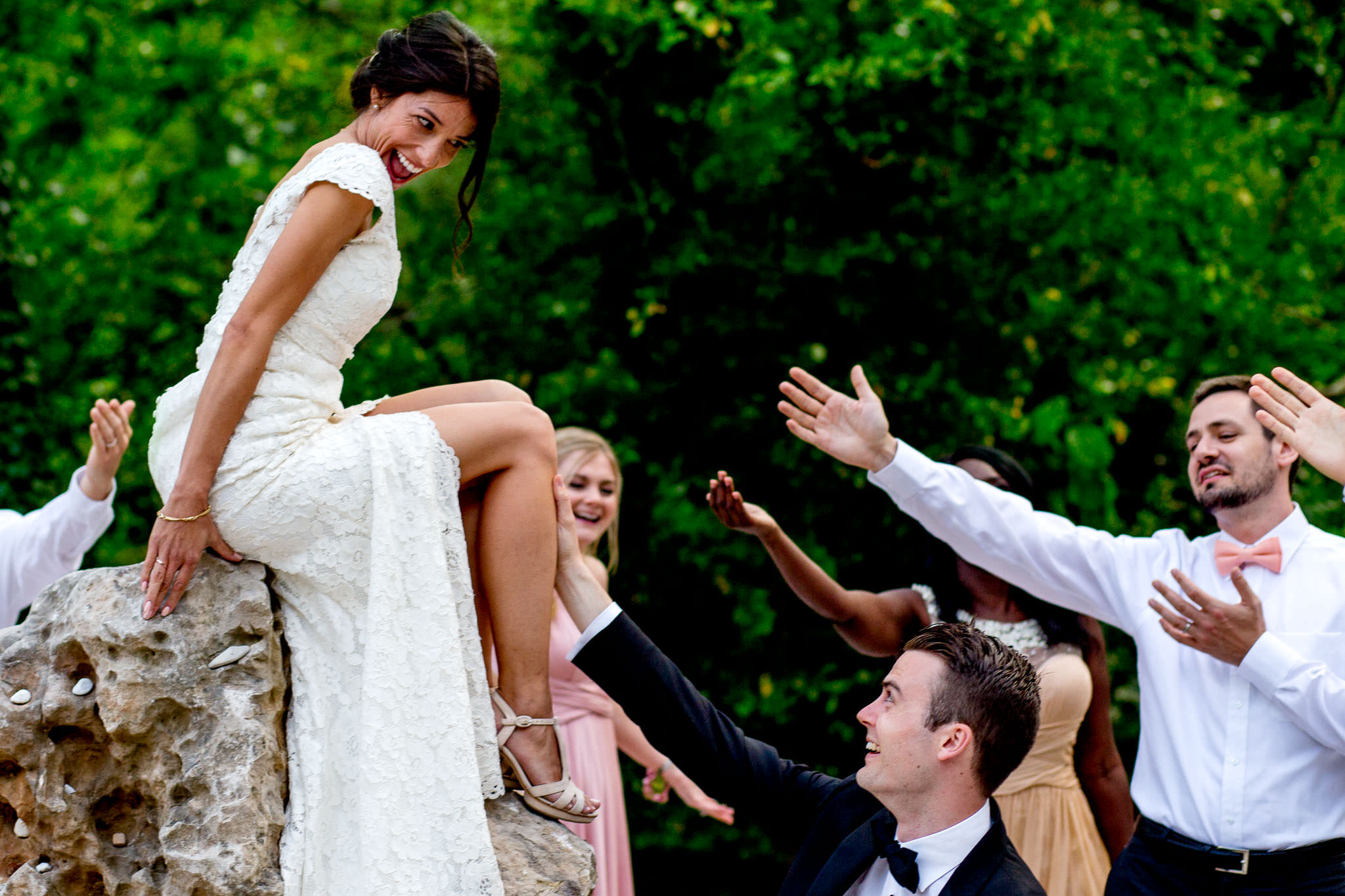 Bride laughing with bridal party at chateau wedding in Cirque de Navacelles outside Montpellier France