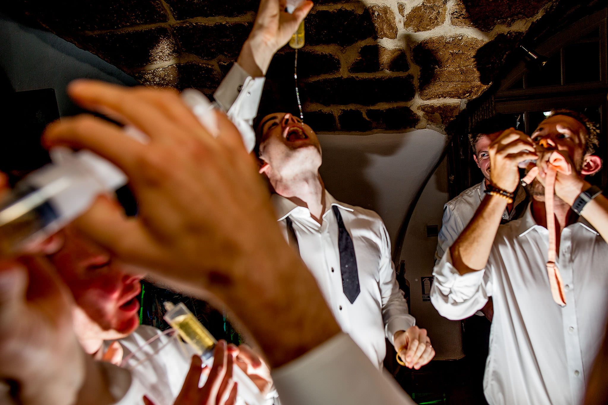 Groomsmen laughing with surrenges spurting with tequilla at chateau wedding in Cirque de Navacelles outside Montpellier France