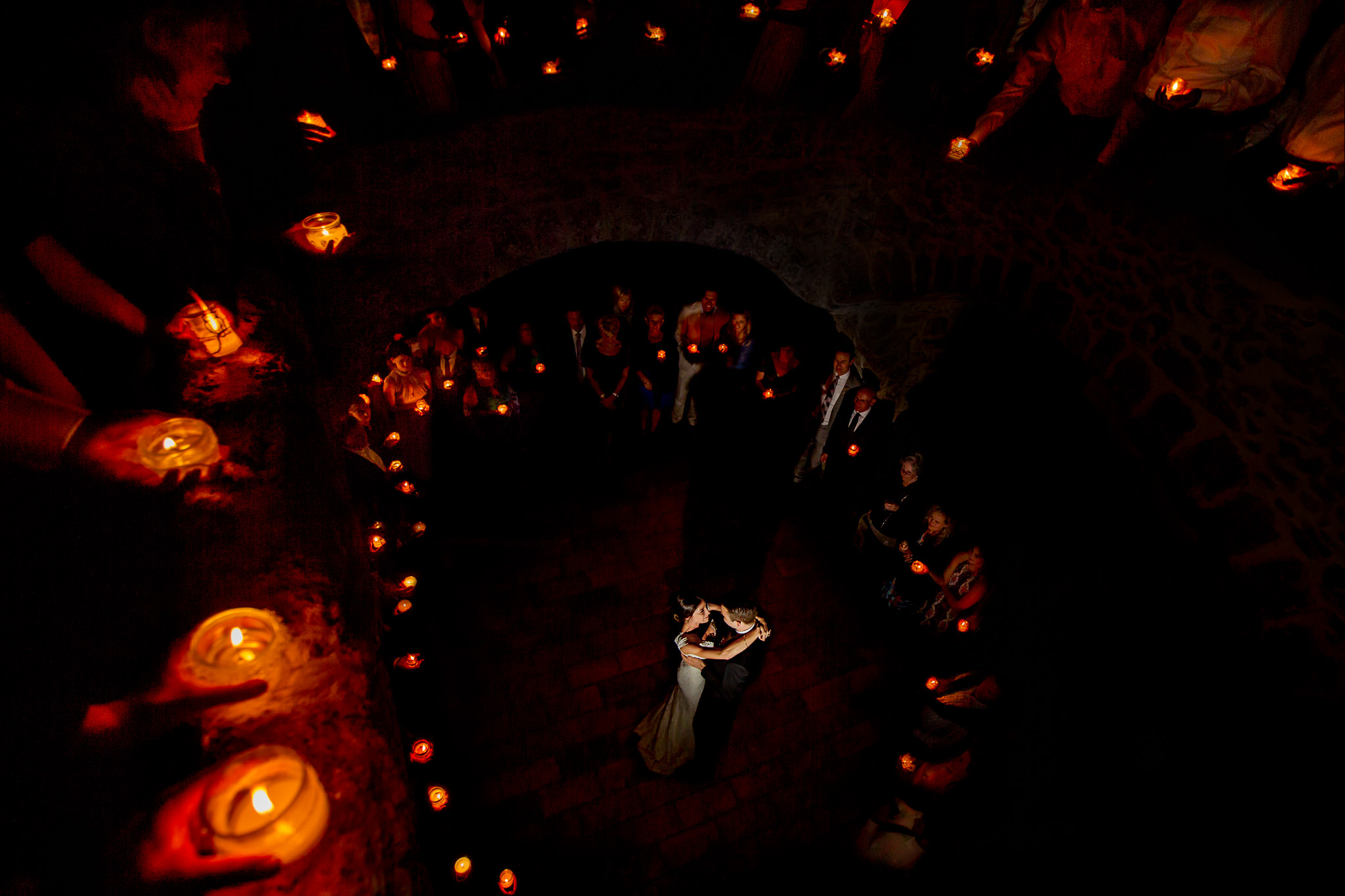 Epic wide angle shot of bride and groom dancing in chateau with guests holding candles from 2 different levels om chateau in Cirque de Navacelles outside Montpellier France