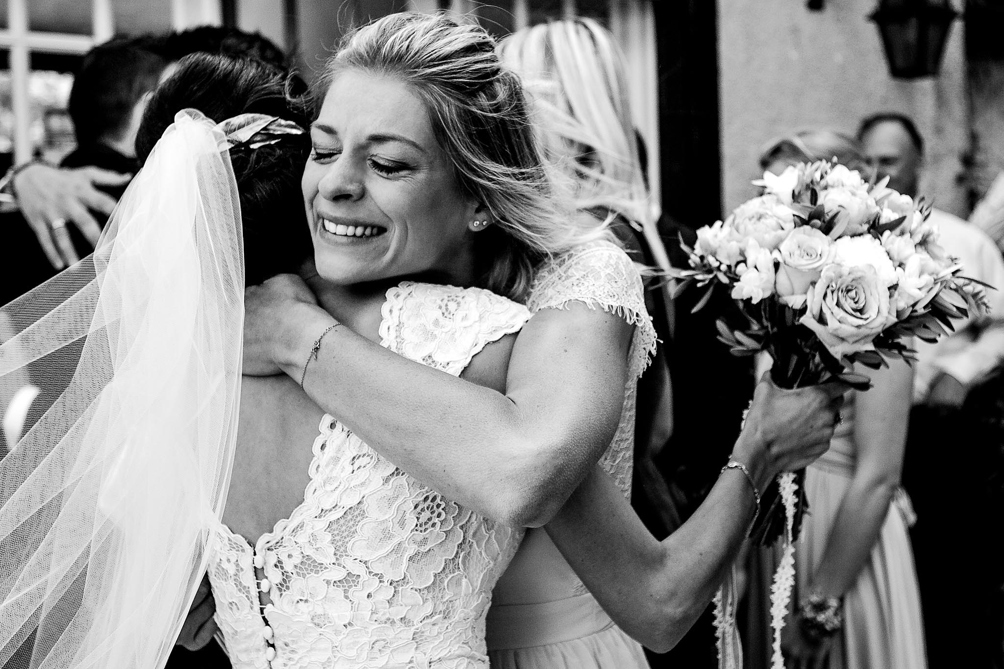 Emotional bridesmaid at French wedding hugging bride