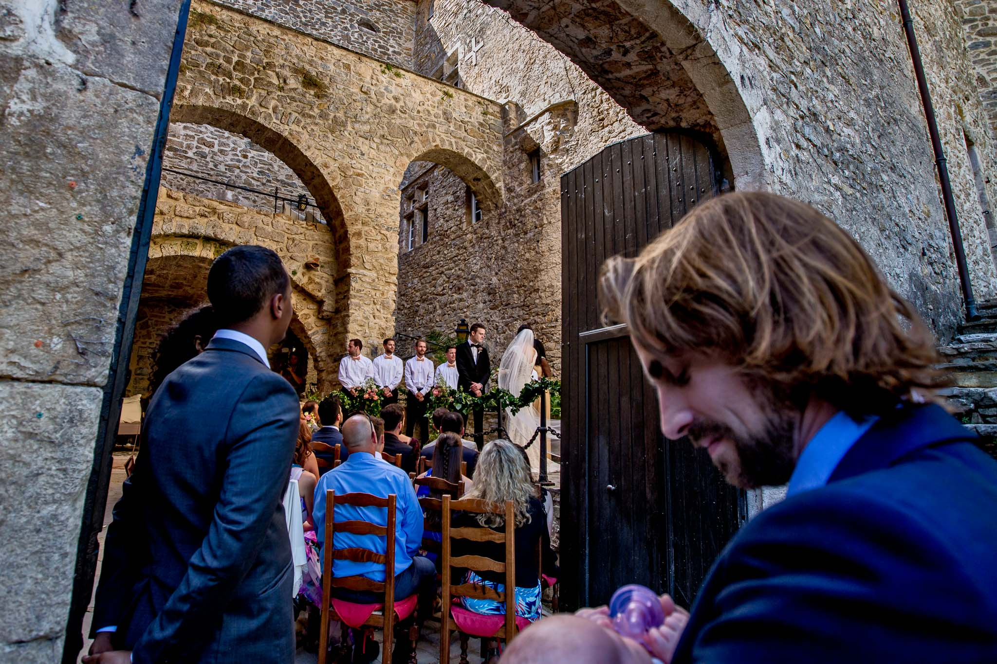 Father holding child during chateau wedding ceremony near Montpellier France