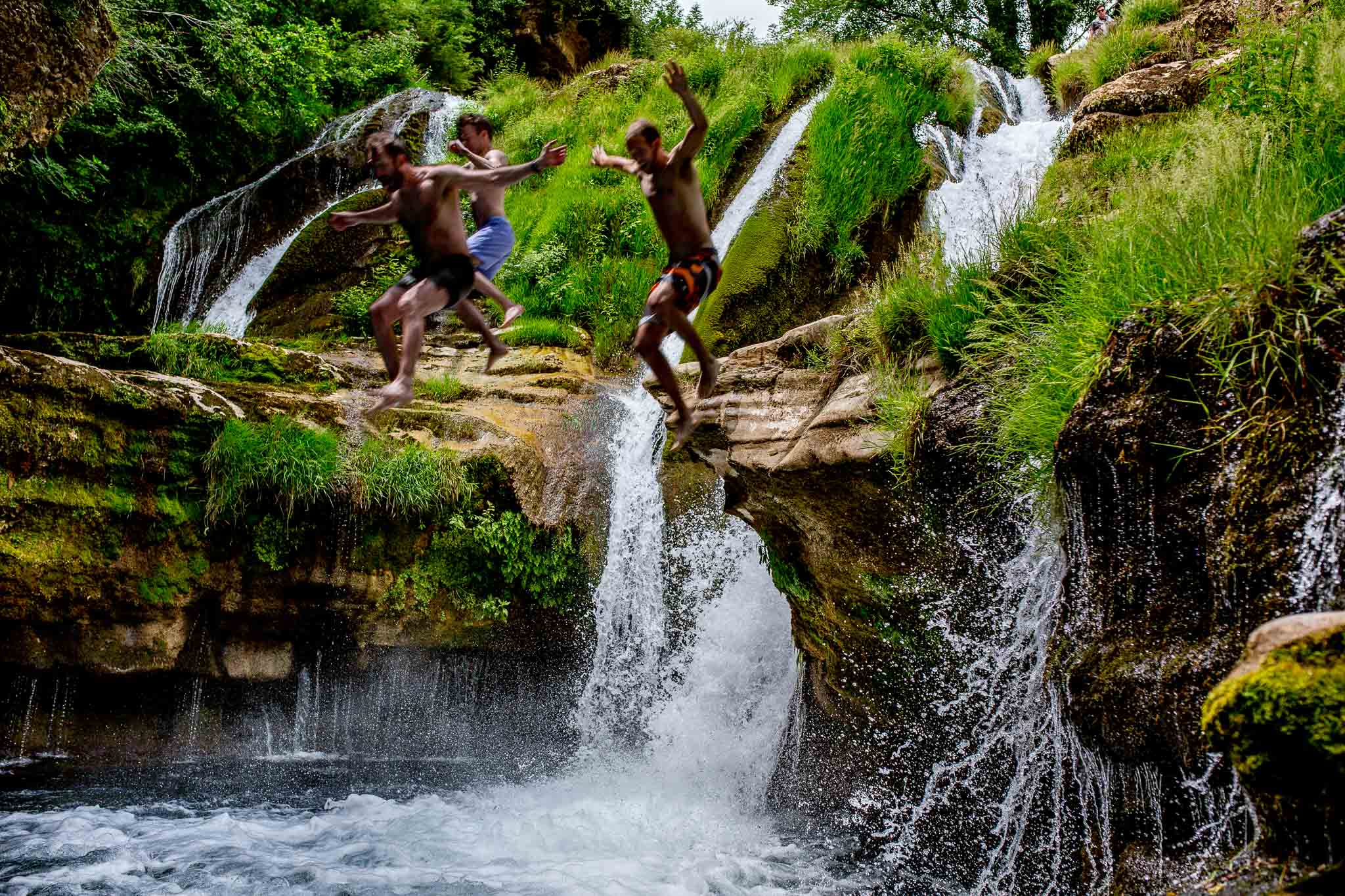 Groomsmen jumping into water in Cirque de Navacelles outside Montpellier France