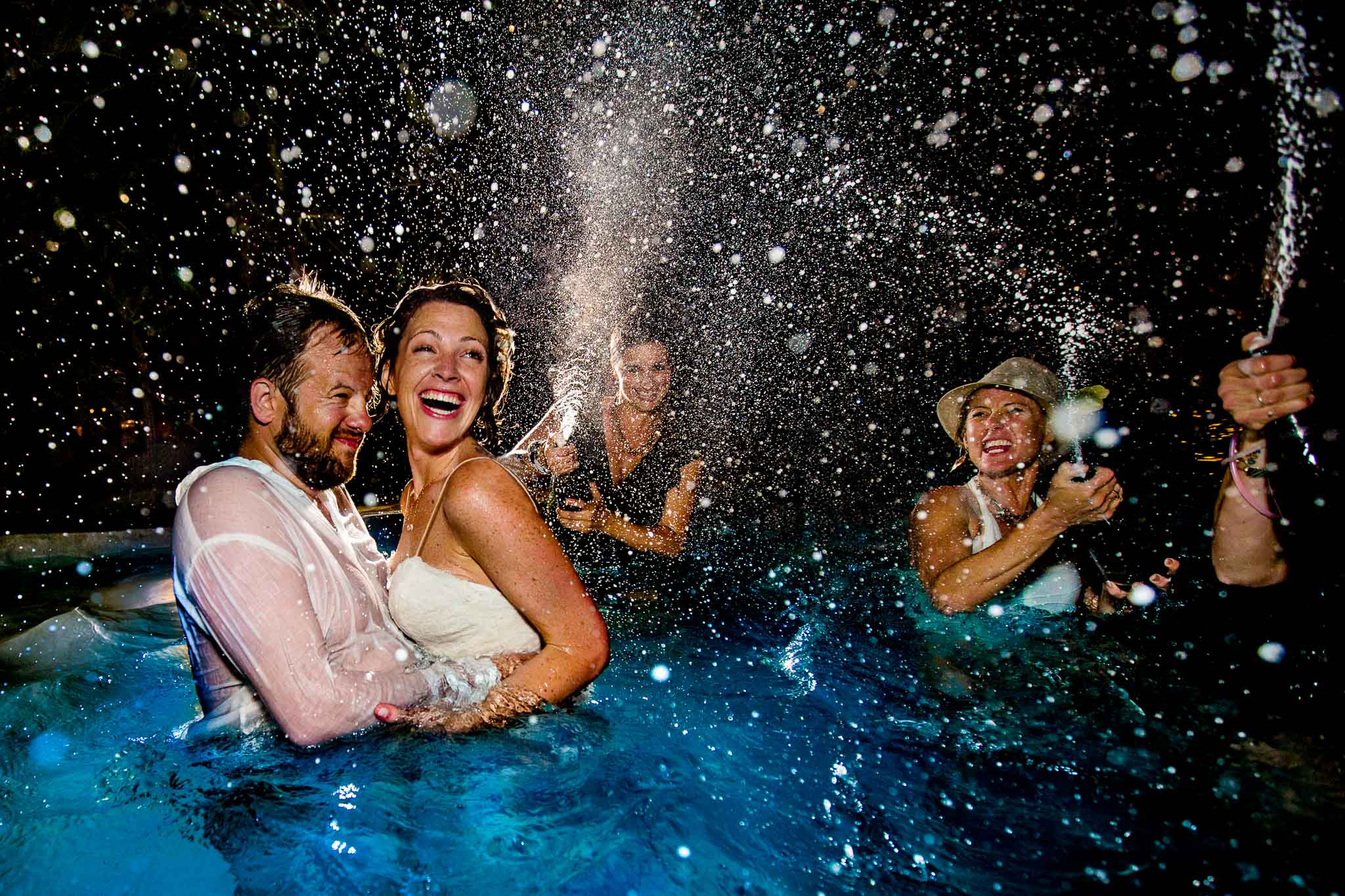 award winning wedding photo bride and groom champagne toast in pool with spray