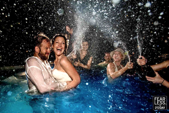 Bride and Groom ecstatic in pool with champagne spraying everywhere with friends - Fearless Photographers Photo of the Day