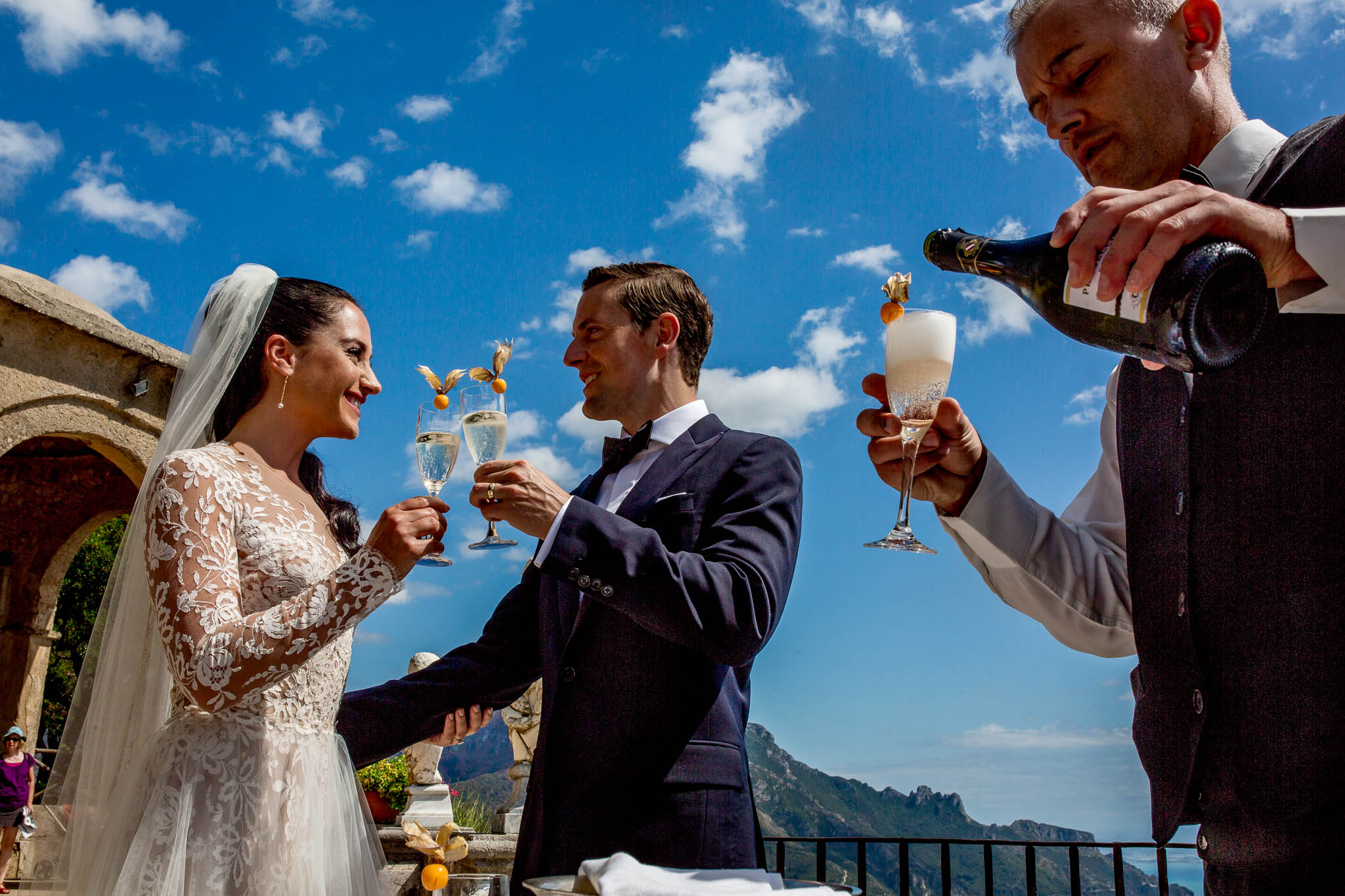 Bride and Groom enjoying champagne on Villa Cimbrone terrace overlooking Amalfi Coast in Ravello Italy