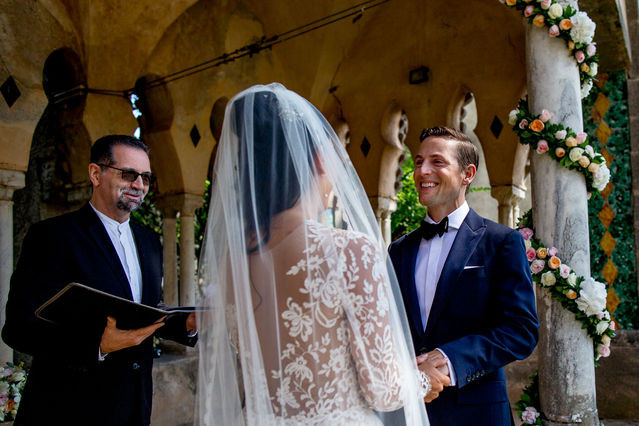Happy groom receiving vows during wedding ceremony at Villa Cimbrone in Garden along Amalfi Coast in Italy