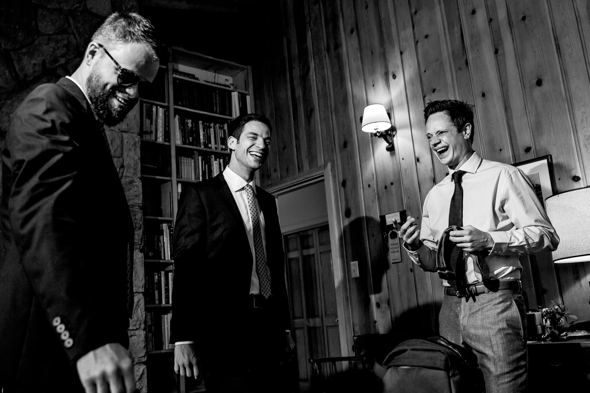 Groom and groomsmen laughing while getting ready at House on Metolious near Sisters Oregon