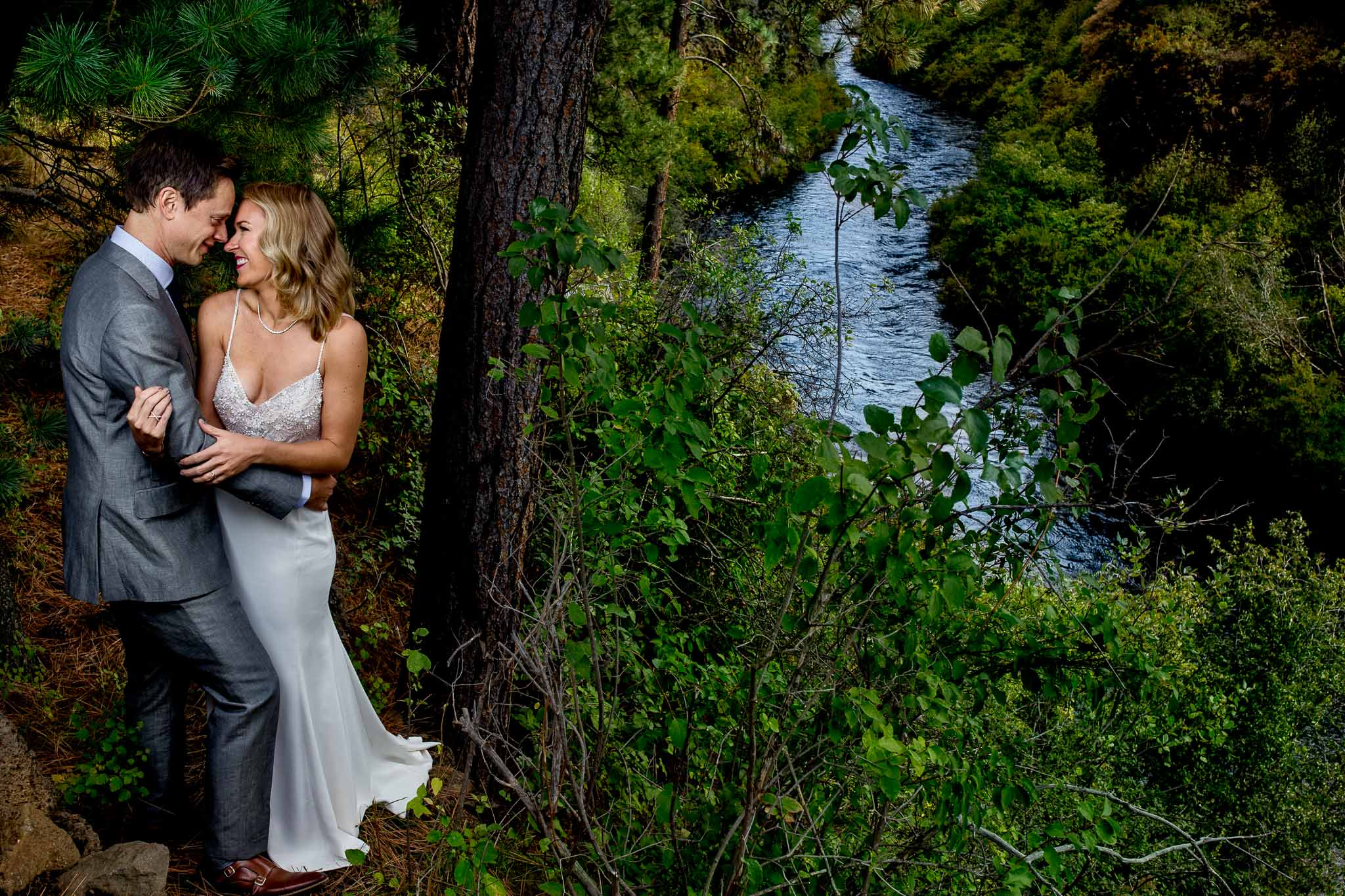 Bride and Groom embracing near Metolious River at House on Metolius