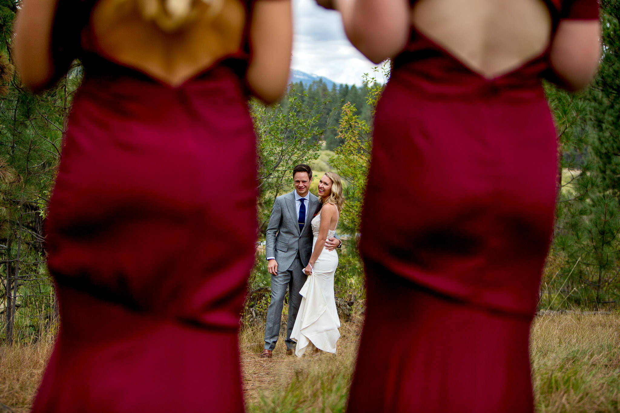 Bride and Groom seen through two bridesmaids in dresses