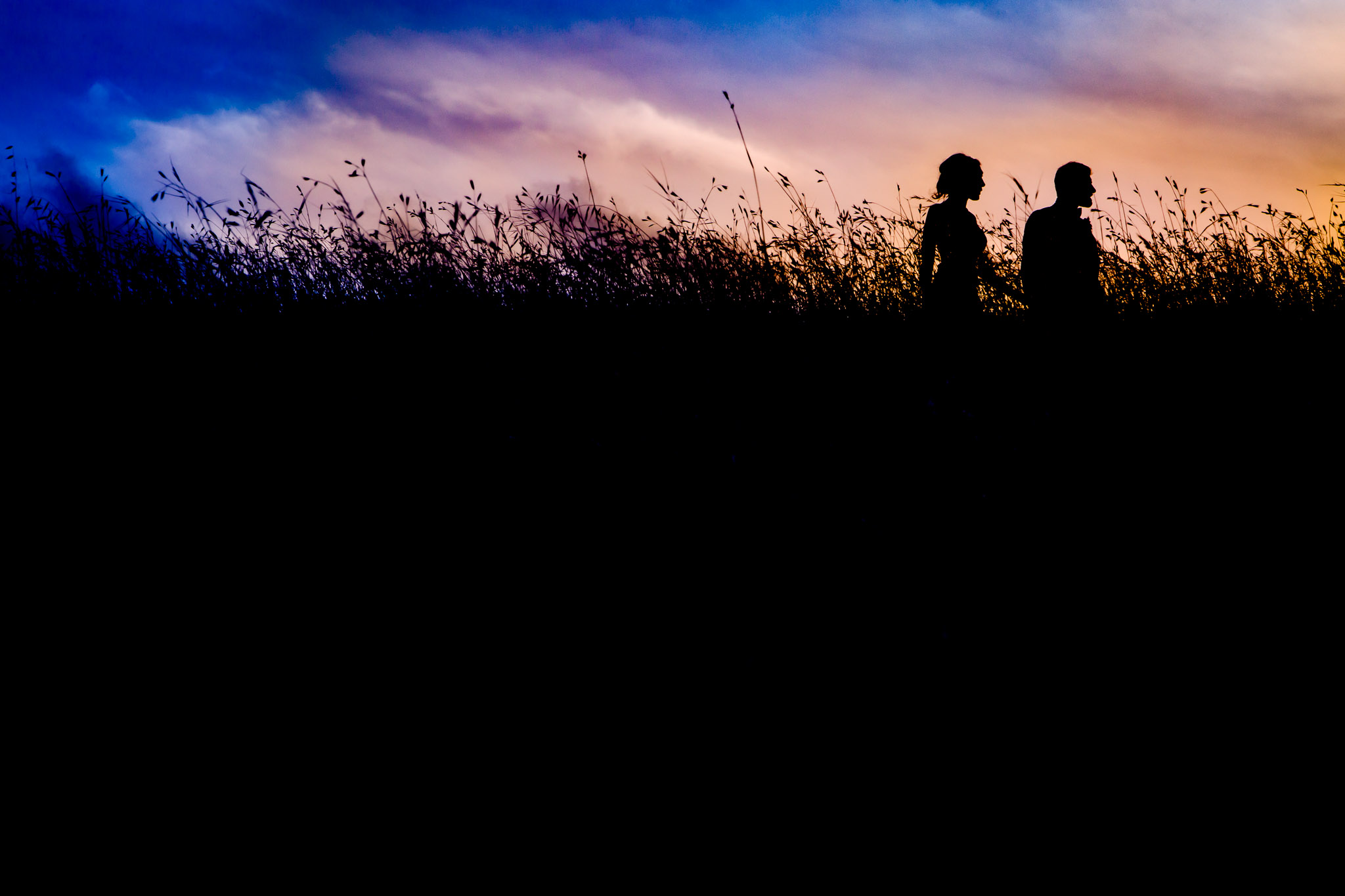 Bride and Groom walking at sunset gorgeous silhouette