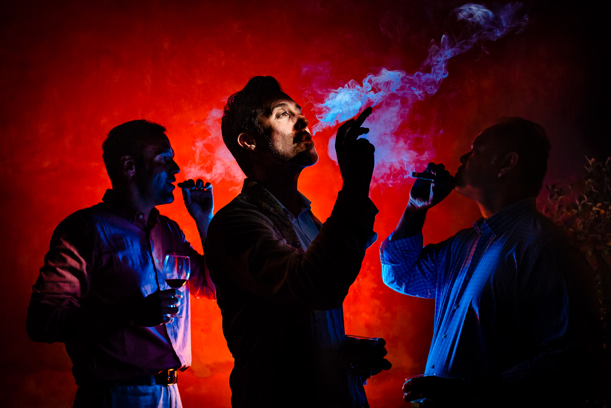 Groomsmen smoking cigars in dramatic colored light in Italy