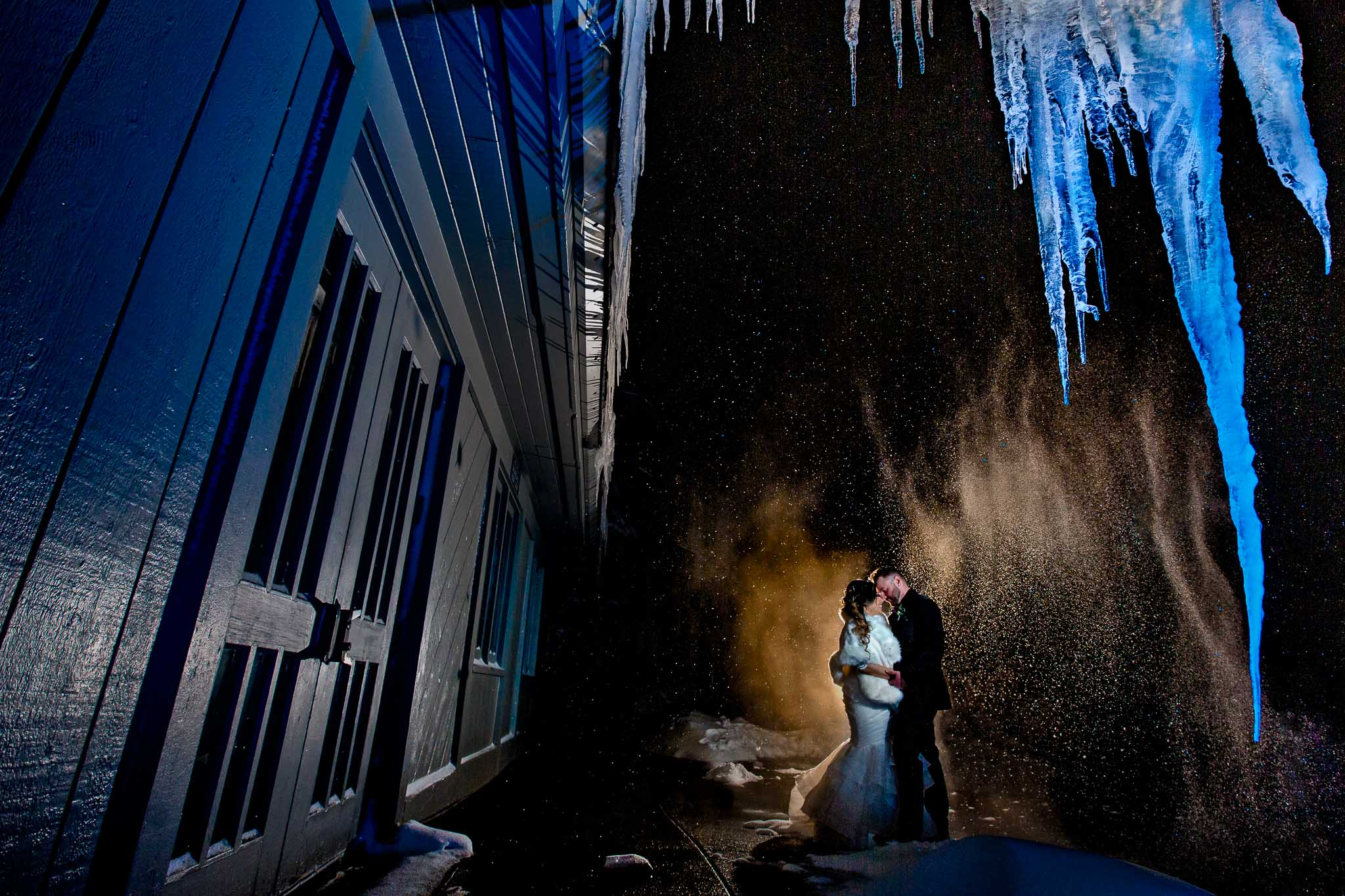 Creative photo of bride and groom under icicles at night at Timberline Lodge just after their Ravens Nest wedding ceremony