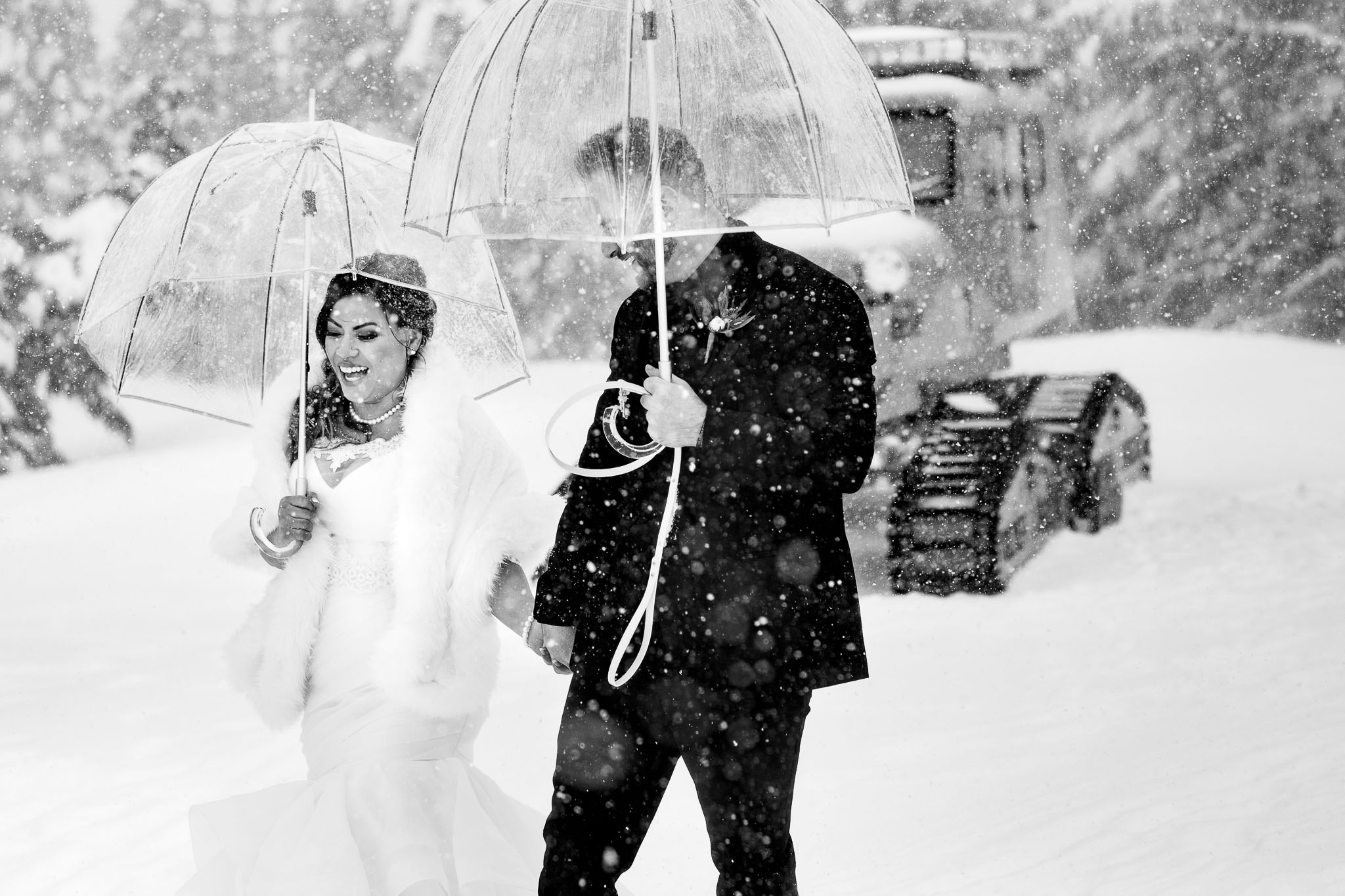 Bride and Groom walking in falling snow outside Timberline Lodge just before entering their ceremony in the Ravens nest