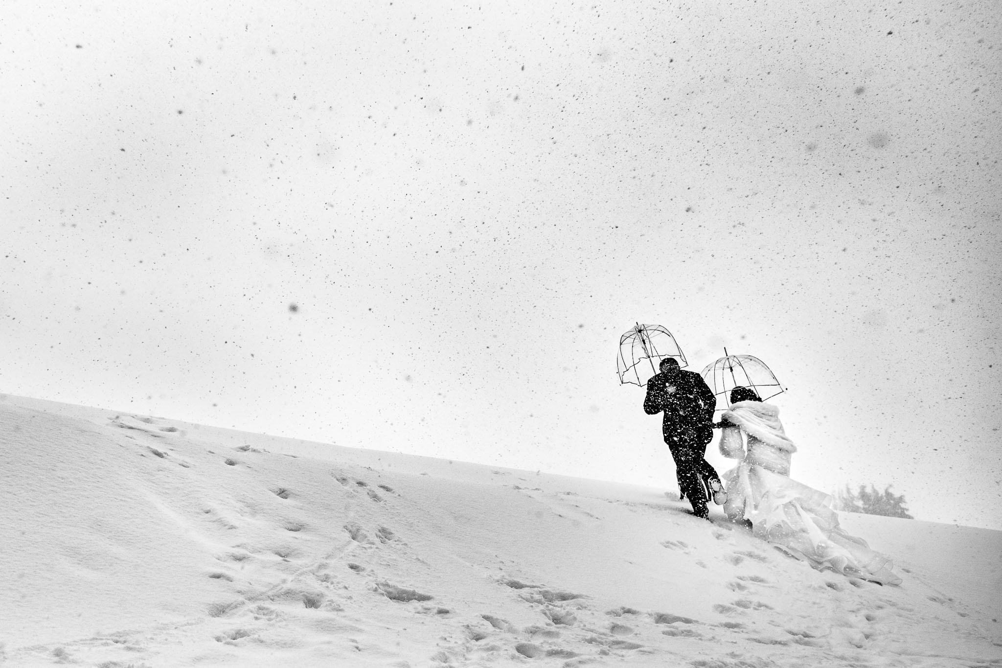 Bride and Groom climbing up snow hill with falling snow outside Timberline Lodge
