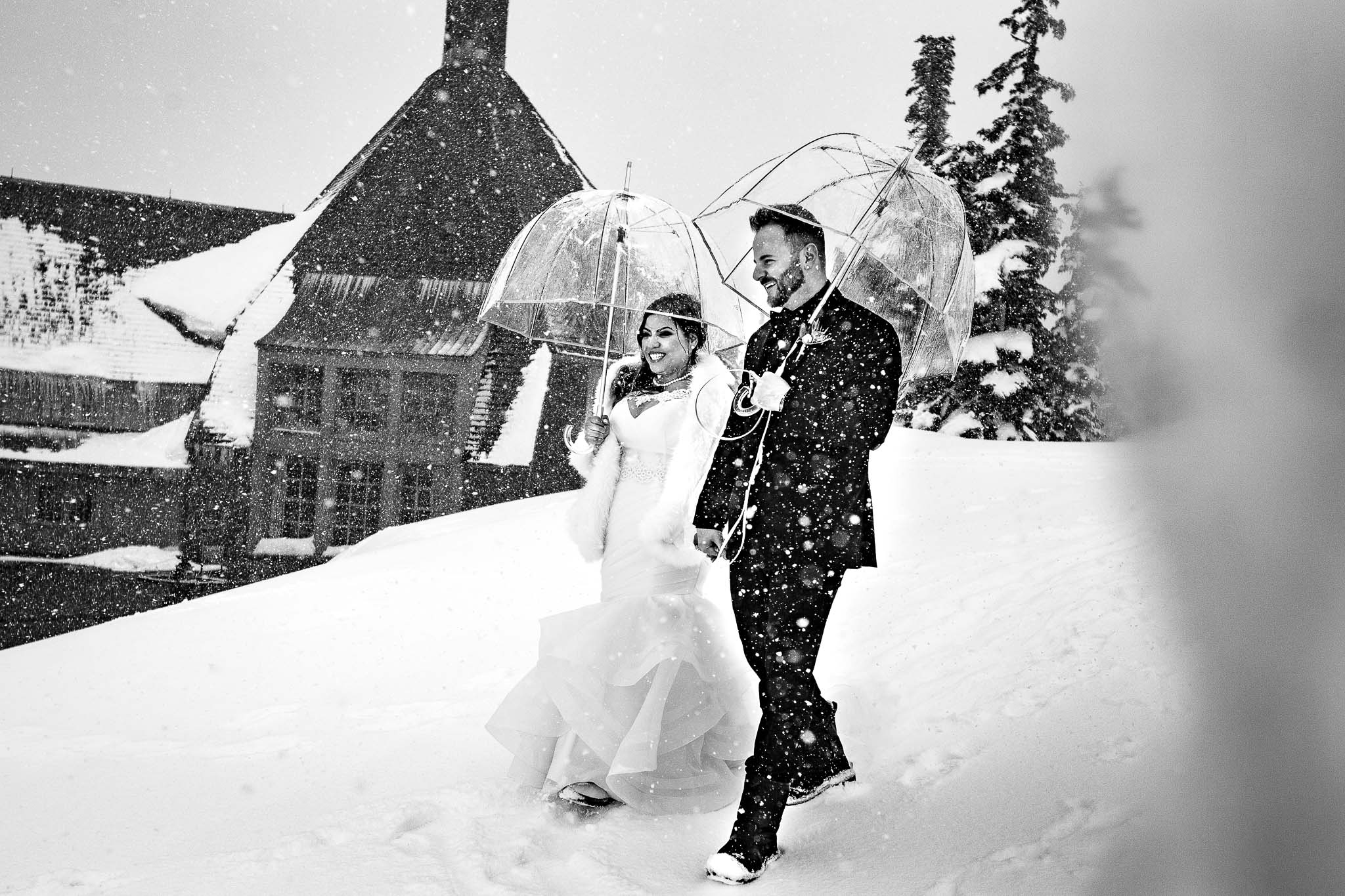 Bride and Groom walking in falling snow outside Timberline Lodge just before their ceremony in the Ravens Nest