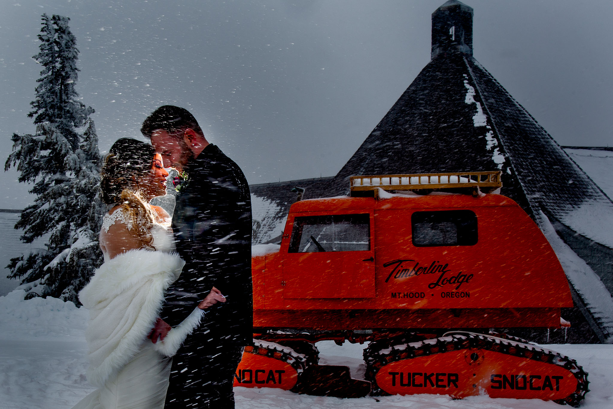 Bride and Groom creatively lit in snow near snowcat at Timberline Lodge for their Ravens Nest Wedding