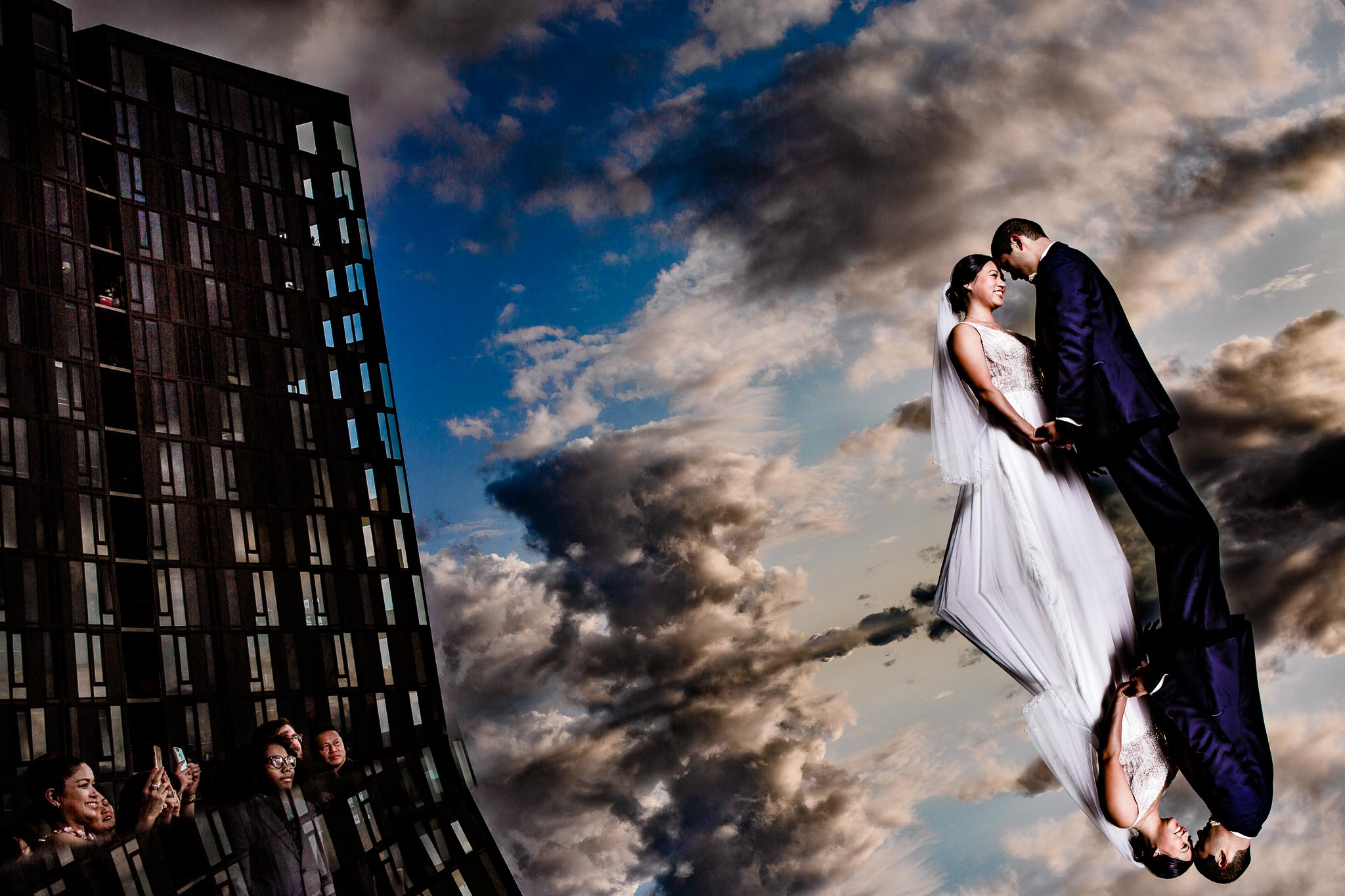 Bride and Groom reflecting in clouds at sunset over reflective building at Exchange Ballroom in Portland