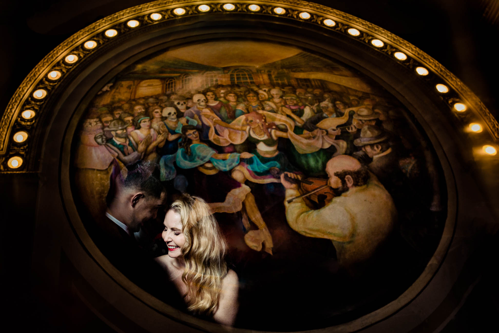 Bride and groom reflecting in mural painting at Crystal Ballroom in Portland Oregon