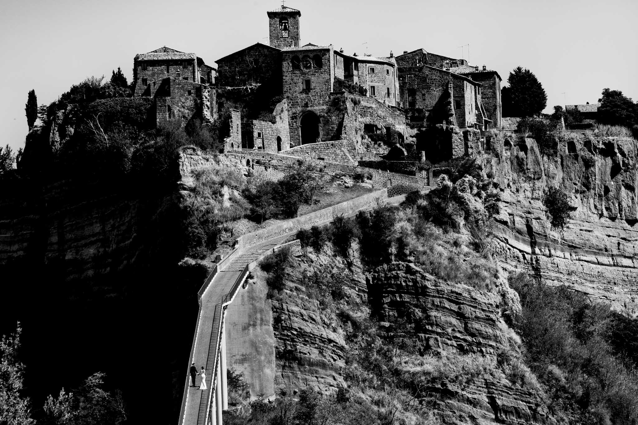 Bride and groom walking up path into Bagnoregio Italy