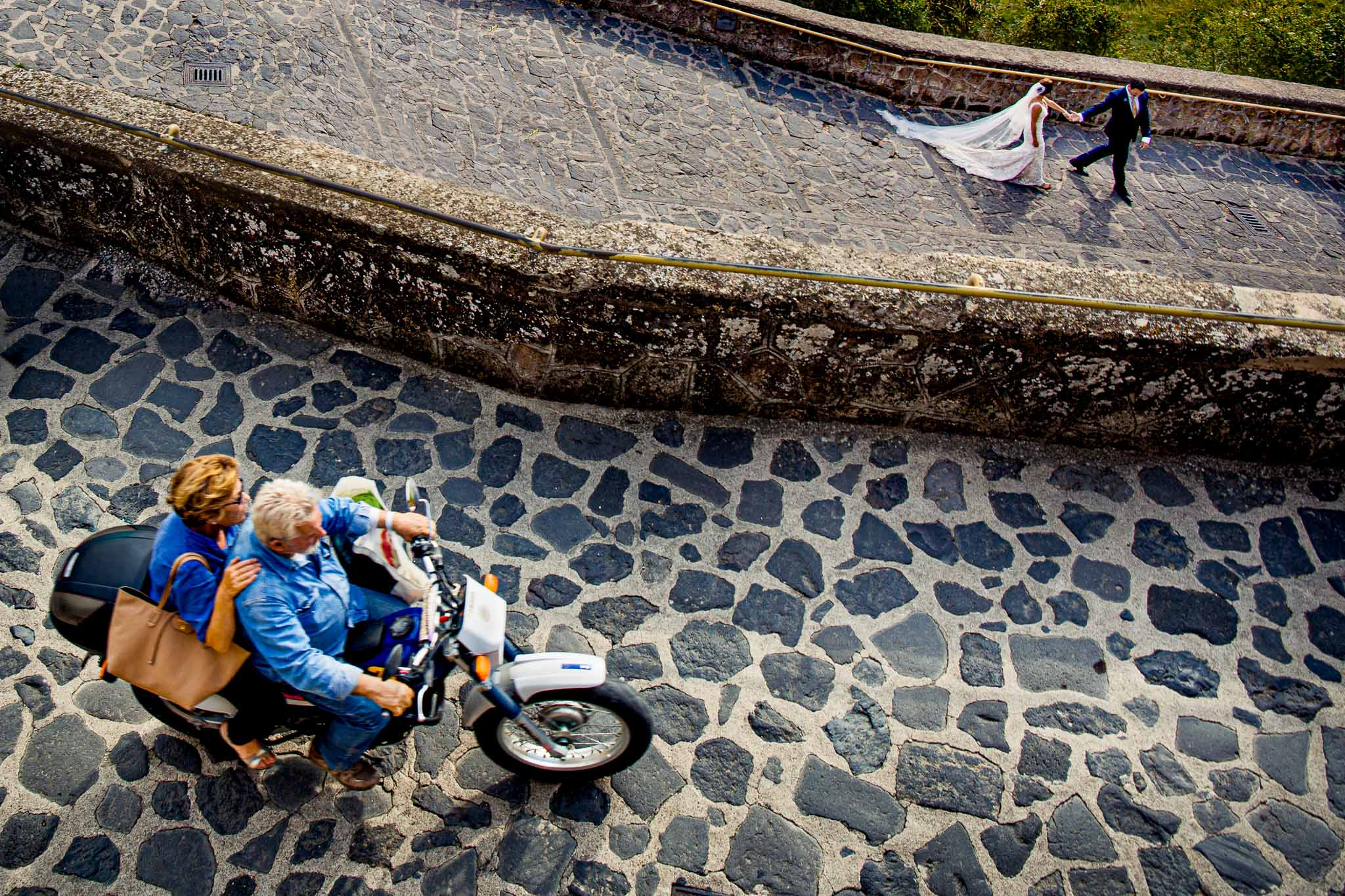 Bride and groom walking up path leaving Bagnoregio Italy with couple on motorcycle.