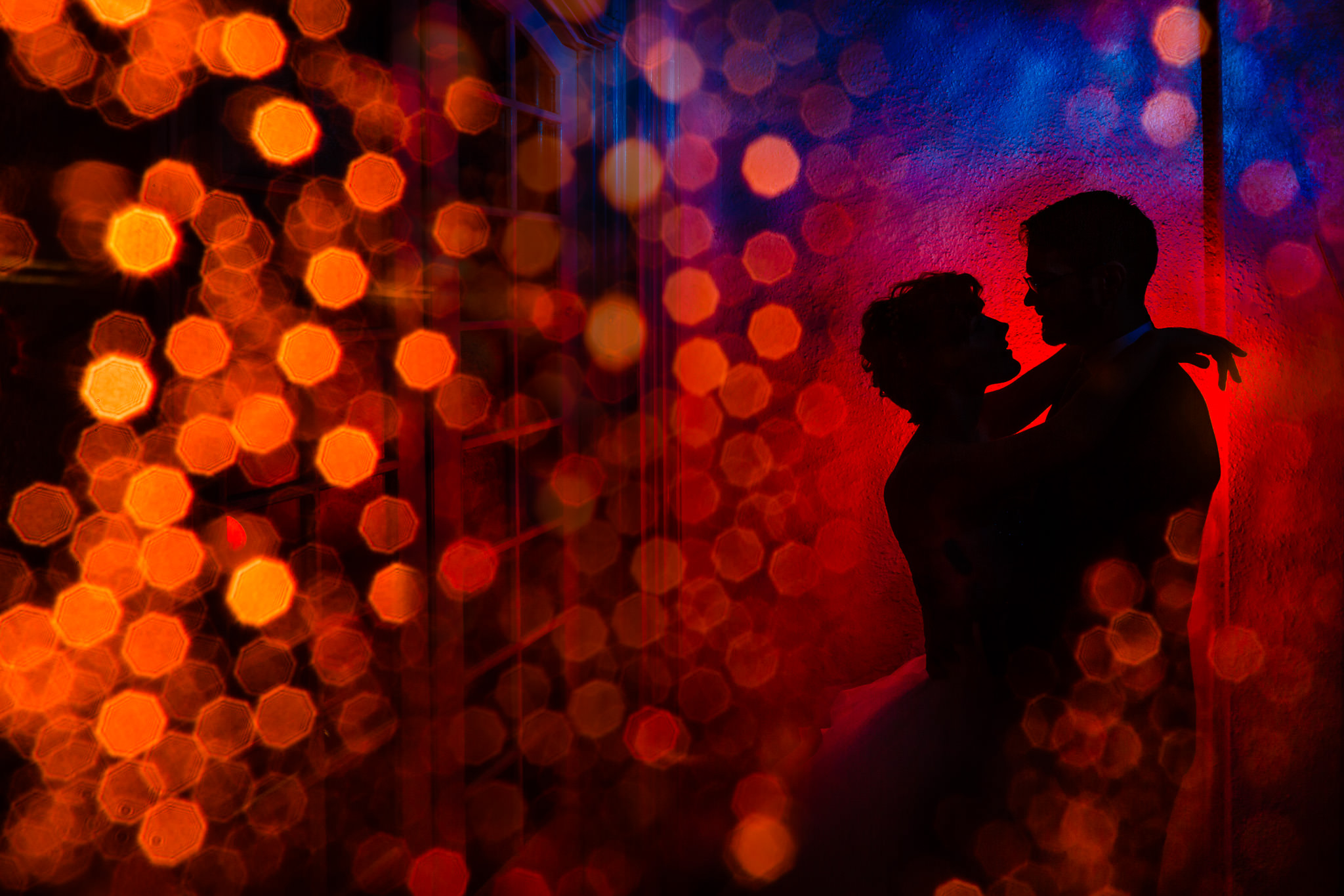 Beautiful abstract colorful photo of bride an groom silhouetted at Portland's White House